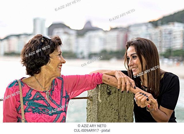 Mature woman holding hand of her mother at beach, Copacabana, Rio de Janeiro, Brazil