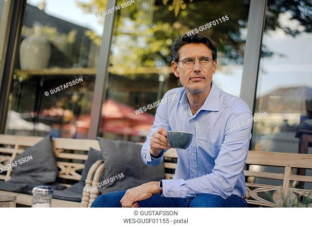 Mature businessman sitting in coffee shop, drinking coffee