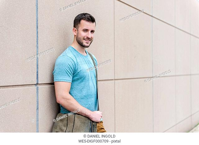Portrait of smiling young man leaning against a wall