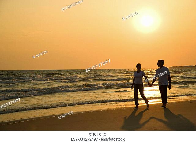 Caucasian mid-adult couple holding hands and walking down beach at sunset