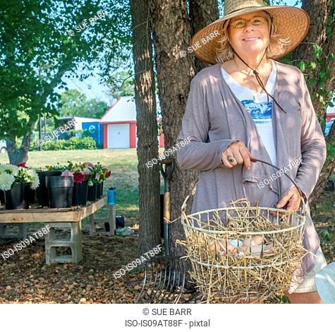Portrait of senior female farmer carrying basket of eggs