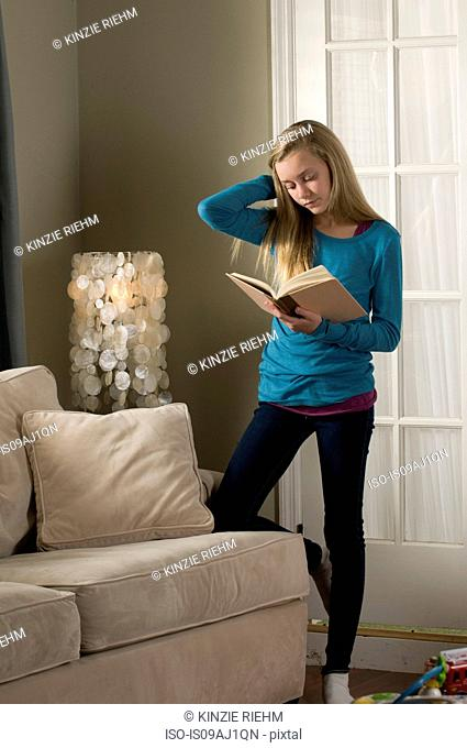 Pre adolescent girl reading book with knee leaning knee