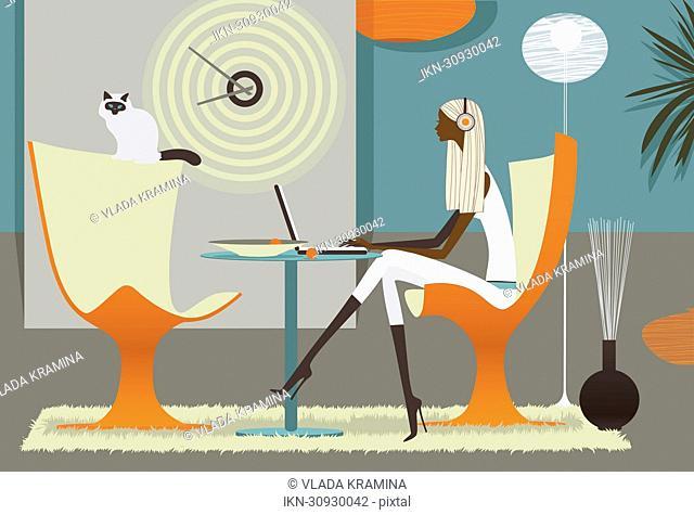Woman listening to headphones on laptop in stylish interior