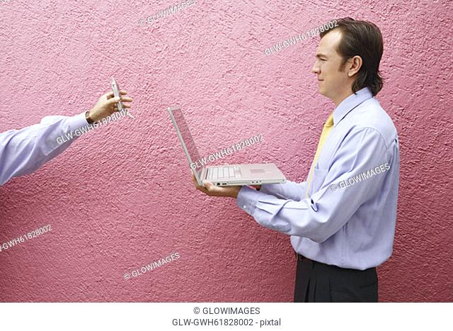 Side profile of a businessman holding a laptop with a person's hand holding a mobile phone