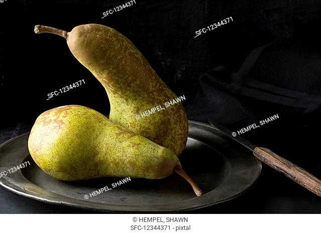 Two Abate Fetel pears on an old tin plate with a knife