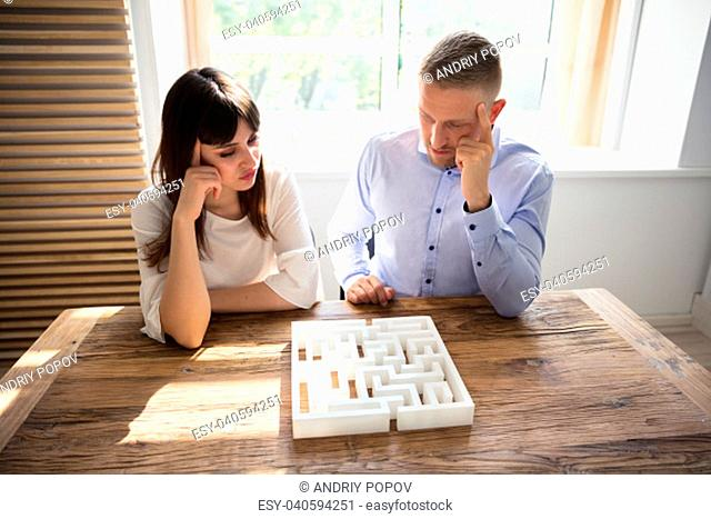 Two Contemplated Young Businesspeople Solving Maze Puzzle Over Wooden Desk