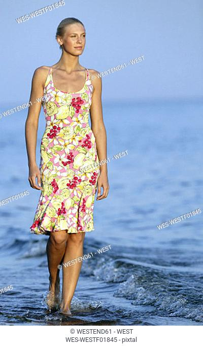 Young woman walking in sea, looking away