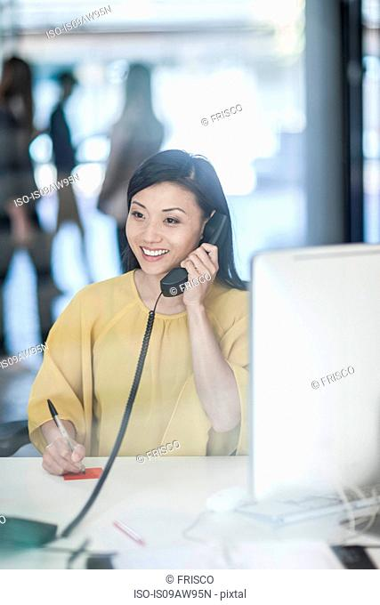 Mid adult businesswoman sitting at desk, using telephone, smiling