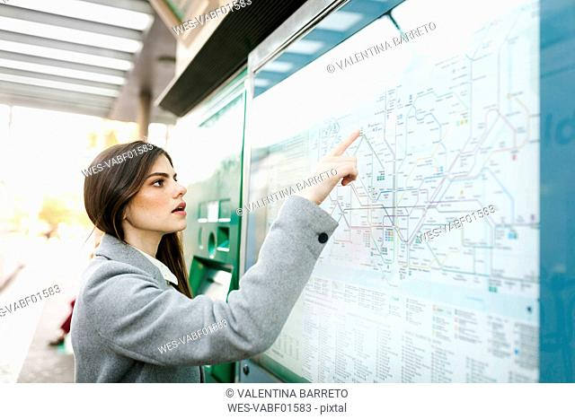 Spain, Barcelona, young woman looking at map at station