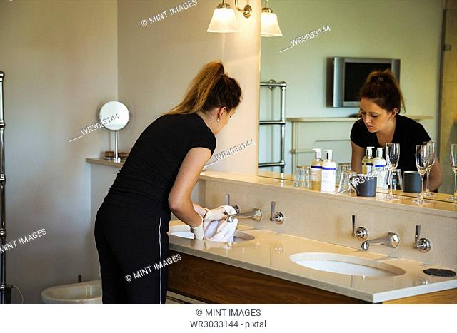 Woman standing in a hotel bathroom in front of mirror, cleaning sink