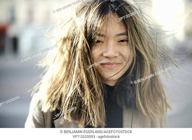young unkempt Asian woman with tousled hairs, bad hair day, in Paris, France