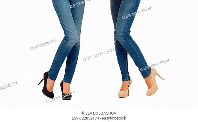 people, fashion, style and clothing concept - close up of two women legs in jeans