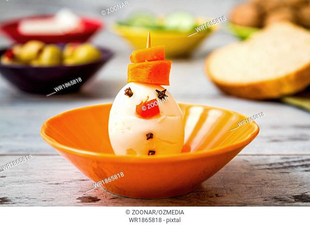 Healthy breakfast with funny snowman from egg and carots