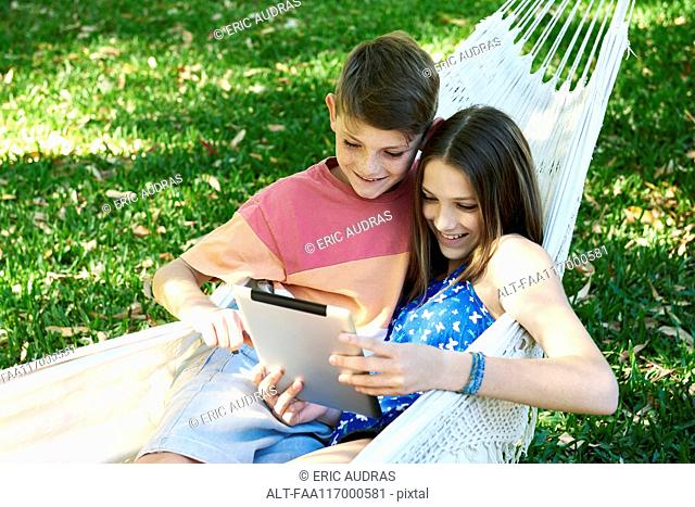 Brother and sister using a digital tablet in a hammock