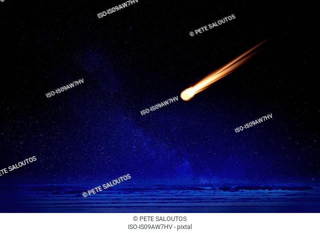 Meteor in night sky falling over ocean