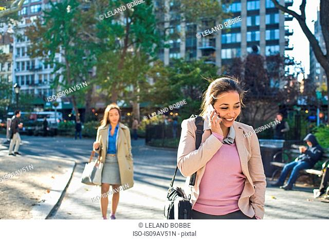 Young woman talking on smartphone whilst walking through city park