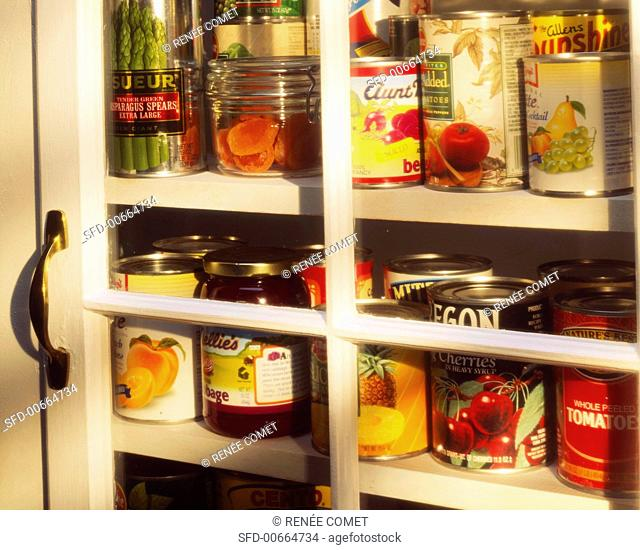 Assorted Canned Goods in a Glass Cupboard