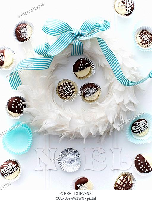 Overhead view of coconut creams in cake cases around feather wreath tied with bow