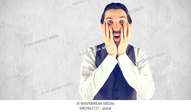 Shocked hipster with hands on face