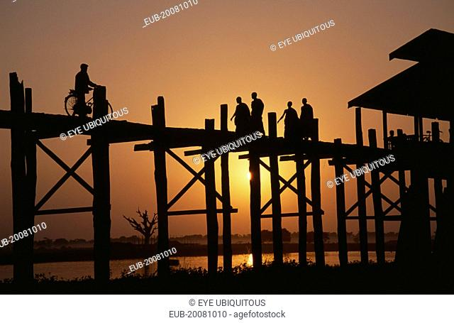 U Bein Bridge near Mandalay at sunset with silhouetted figures of monks and cyclist crossing