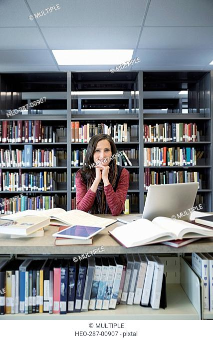 Portrait confident adult education student researching in library