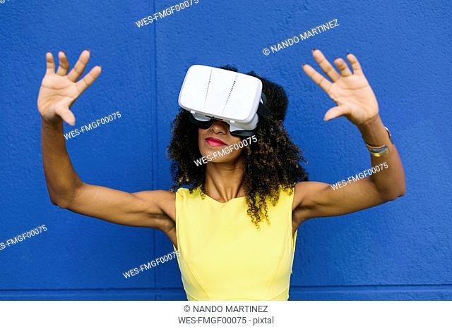 Woman using Virtual Reality Glasses against blue background