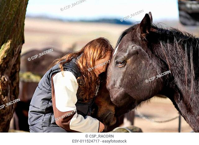 Young girl petting her horse