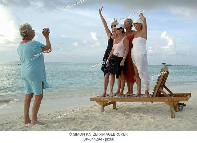 Elderly women filming each other with a video camera on the beach, Diffushi Island, Holiday Island, Southern Ari Atoll, Maldives, Indian Ocean