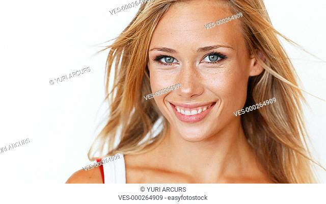 A gorgeous young blond woman smiling at you