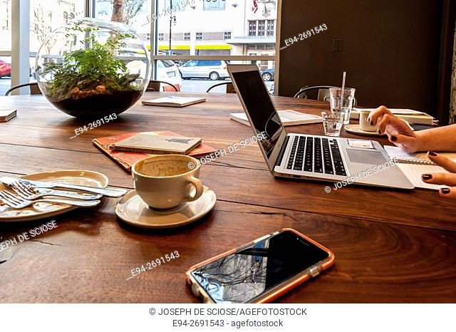 Coffee shop vignette showing a cell phone, laptop computer and coffee cup and other table top items.Birmingham, Alabama, USA