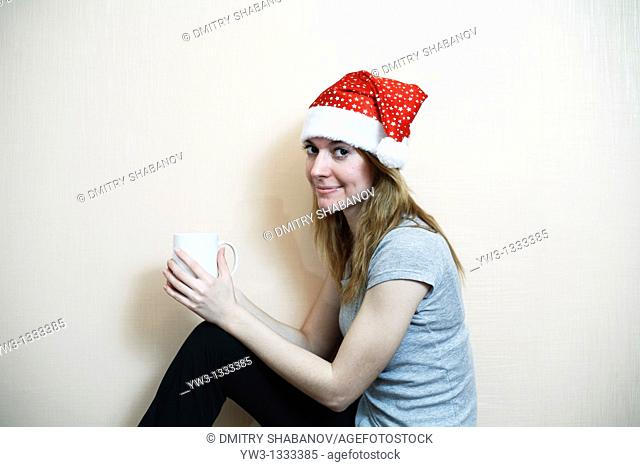 pretty girl in the Christmas hat against light wall with cup of tea or coffee