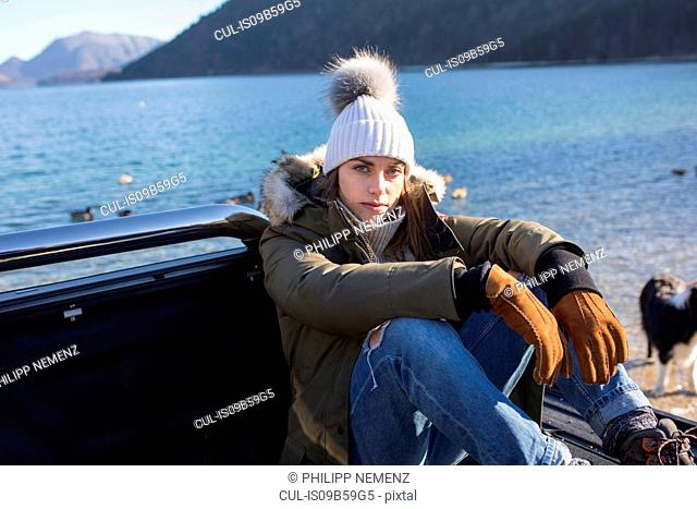 Portrait of woman sitting on pick up at lakeside in Bavarian Alps
