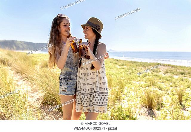 Two friends toasting with beer bottles on the beach