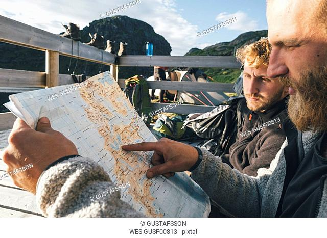 Norway, Lofoten, Moskenesoy, Young men discussing directions, holding map