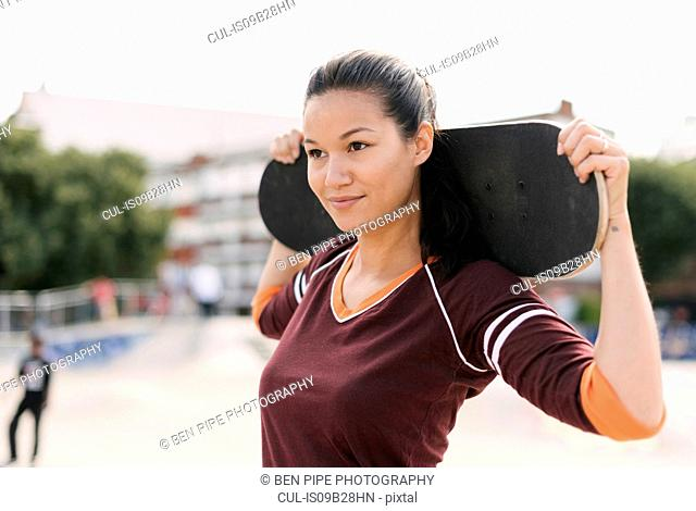 Portrait of female skateboarder carrying skateboard on shoulders