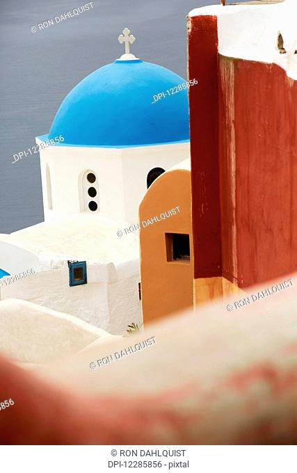 Greek orthodox church with blue dome in the village of Oia; Oia, Santorini, Greece