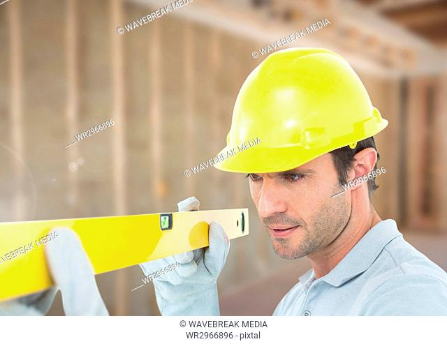 Construction Worker with spirit level in front of construction site