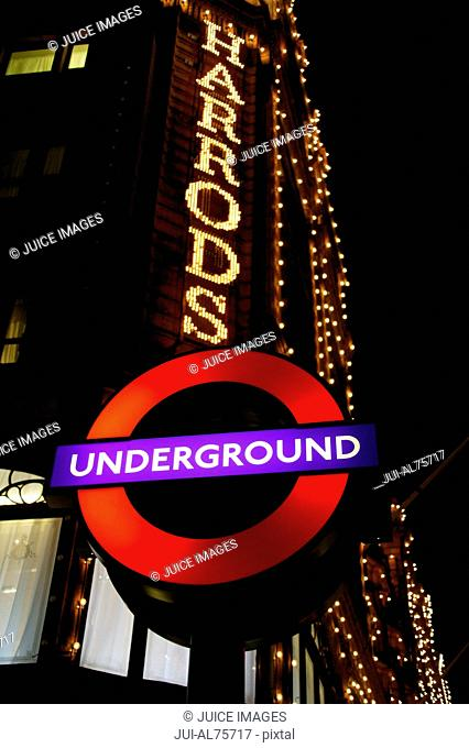 Low angle view of Underground sign and Harrods sign at night, London, United Kingdom
