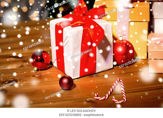 christmas, holidays, presents, new year and celebration concept - group of gift boxes and red balls on wooden board over lights