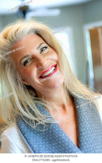 A pretty 52 year old blond woman look smiling at the camera