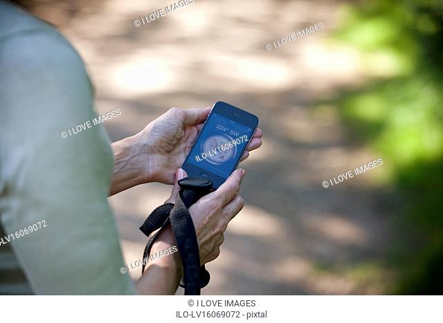 A woman holding a smartphone with a compass application, close up