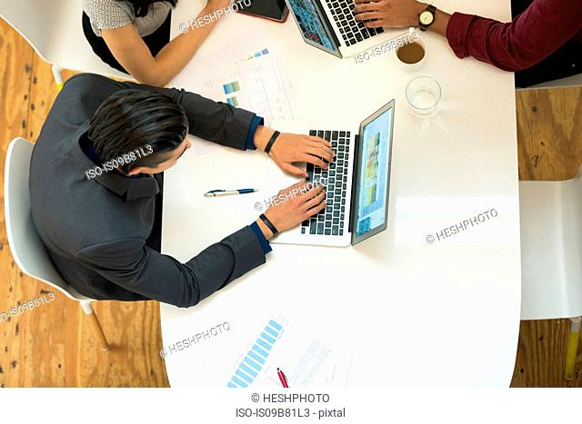 Overhead view of businessman typing on laptop at office table