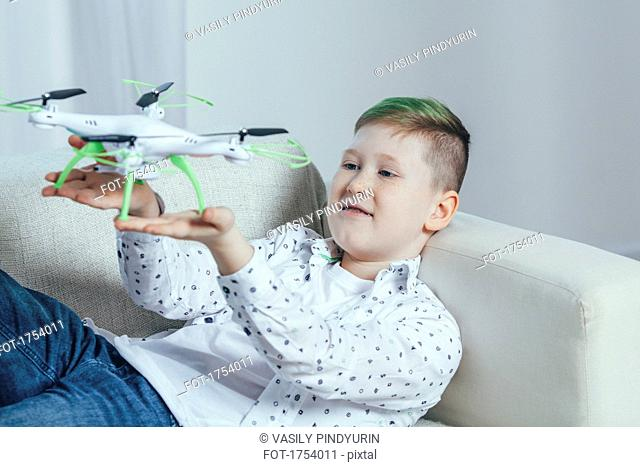 Smiling boy lying on sofa holding drone in living room at home