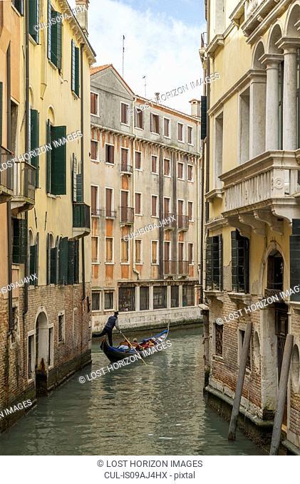 Gondolier on narrow canal, Venice, Veneto, Italy