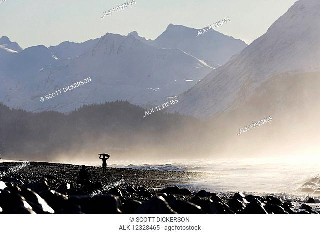 Female surfer carries her surfboard over her head along the Homer Spit beach, South-central Alaska; Homer Spit, Alaska, United States of America