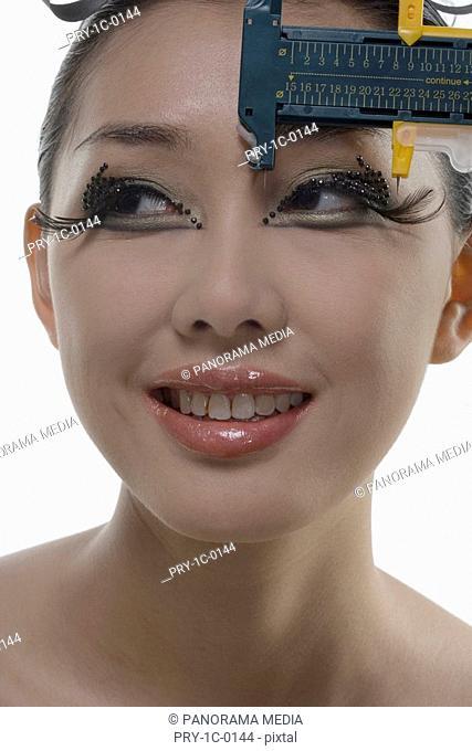 Vernier calliper measuring woman's eyelid, close-up