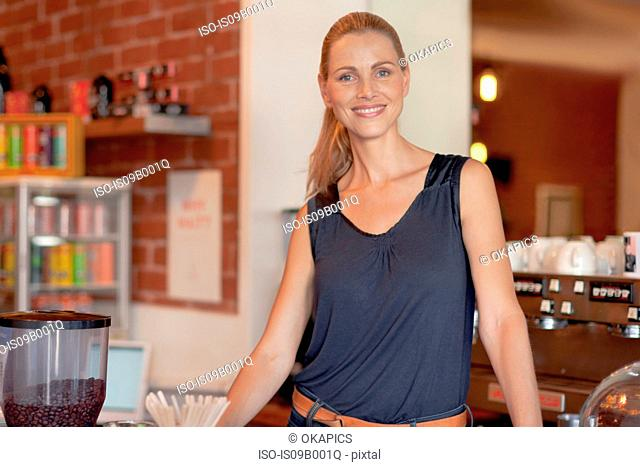 Portrait of mature woman behind counter in cafe