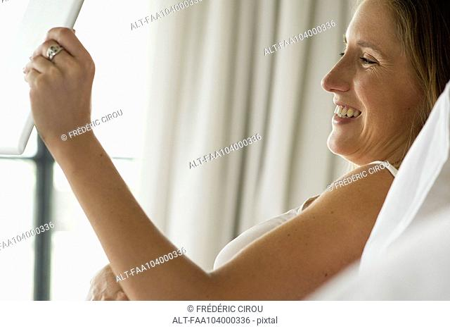 Pregnant woman using digital tablet to video chat with friends and family