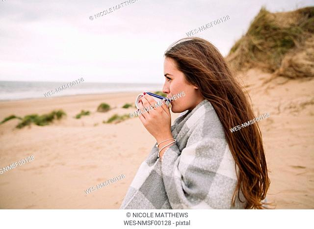 Young woman with cup of hot chocolate on the beach