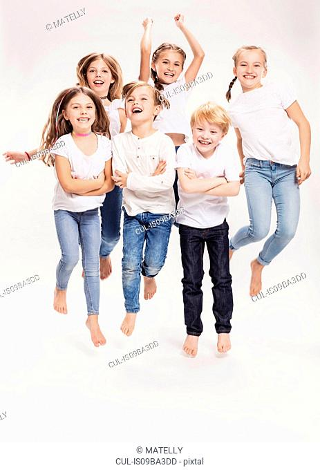 Studio portrait of two boys and four girls having fun jumping mid air, full length